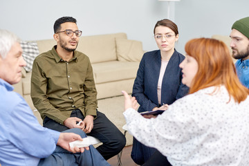 Profile view of red-haired obese woman discussing faced problem with other patients while participating in group therapy session, pretty psychologist listening to her with concentration