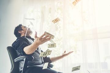 happy business man earned dollar bills us money under a money rain
