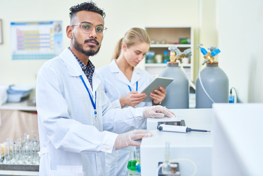 Serious handsome young Arabian scientist in lab coat choosing program for machine while working in laboratory, his female assistant using tablet behind him