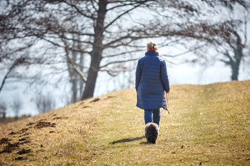 Woman walking away with dog looking from behind sad