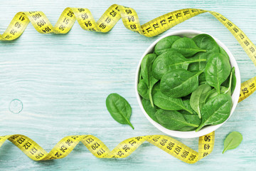 Green spinach leaves and tape measure on wooden table top view. Diet and healthy food concept.