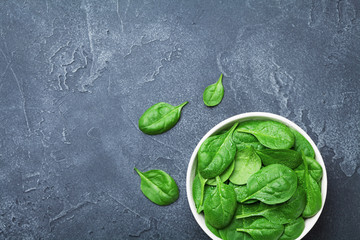 Green spinach leaves in bowl on black table from above. Organic food.