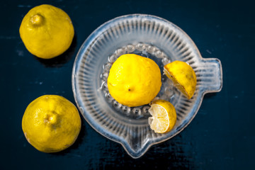 Raw fresh ripe lemons or Citrus × limon in a glass squeezer on black wooden surface in dark Gothic colors.