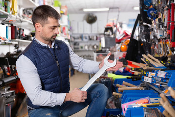 Man is choosing new wrench in tools store.