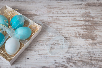 Blue Easter eggs on white old table. Concept of Easter and spring