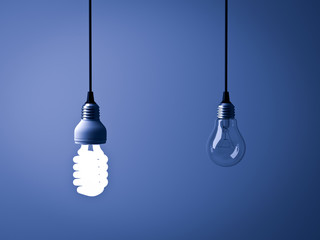 Eco energy saving light bulb , one glowing compact fluorescent lightbulb and unlit incandescent bulb on dark blue background . 3D rendering.