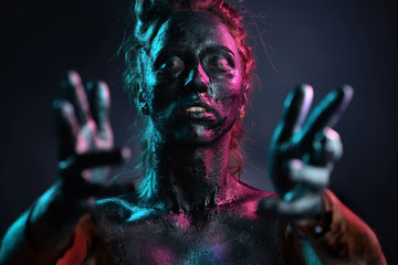 woman with a painted black skin on a black background with neon light