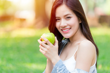 Beautiful Asian women model hand hold Green Apple in park outdoor healthy eating organic food fruits diet concept