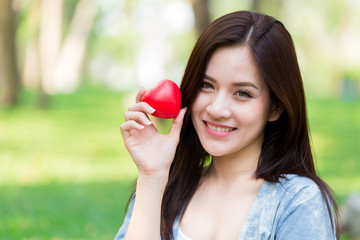 Cute Asian woman hold red heart for loving share love together concept
