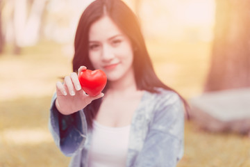 Cute Asian woman hold red heart vintage colortone for share love together concept