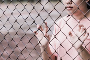 teen behind the cage or woman jailed, unhappy girl hand sad hopeless at fence prison in jail, no free and freedom struggle teen concept.