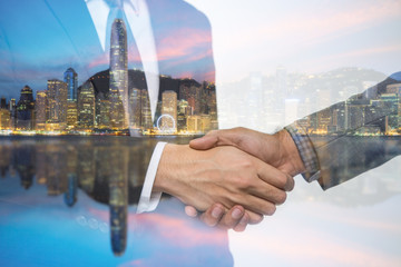 Double Exposure of a businessman handshake on the Hong Kong skyscraper background.