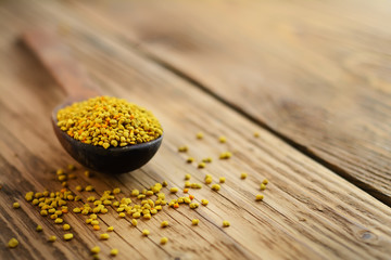 Bee pollen in spoon over wooden background. Healthy organic raw diet vegetarian food ingredient - bee pollen. Apitherapy.