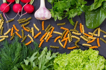 Background with organic vegetables and macaroni. Colored spiral pasta and fresh herbs. Healthy italian food background.