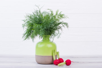 Dill and radishes on white wooden background. Fresh dill in ceramic pot. Beautiful vegetables composition.