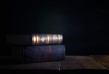 image of stack of antique books over wooden table and dark background.