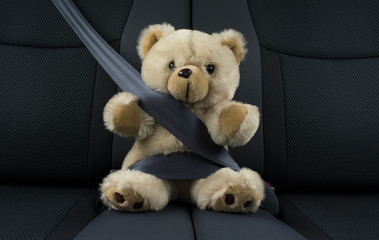 Teddy bear is sitting in a car fastened with a seat belt, represents child safety in a car