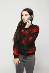 Young brunette teen girl with surprised face talking on the phone