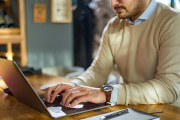 Close up focus view of young businessman in suit typing on a laptop keyboard at the cafe.
