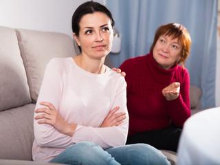 Sad mature female and daughter at sofa after quarrel