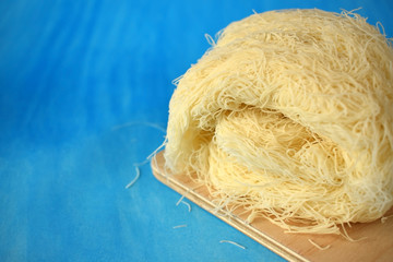Kataifi dough on a wooden board on blue background