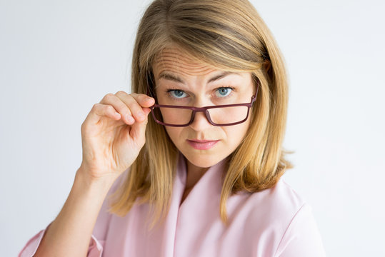 Frowning puzzled teacher looking surprised. Shocked displeased lady looking at camera over her glasses. Serious middle-aged woman wrinkling forehead and adjusting eyewear. Strictness concept