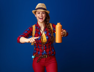 happy tourist woman isolated on blue pointing at water bottle