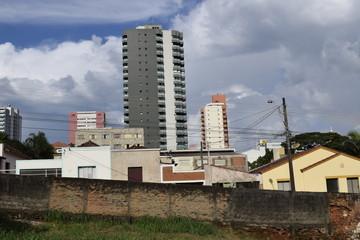 Prédios e casas vistos a partir de terreno baldio no centro de São Carlos