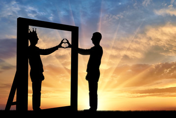 Silhouette of a narcissist man and hand gesture of a heart in reflection in the mirror and crown on his head