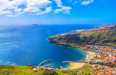 Aerial view of Machico bay in Madeira, with an airplane taking off against the ocean and the coastline of island in Portugal Fototapete