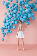 Young woman in white cocktail dress standing back to camera on pink wall background with blue bubbles hanging. Dreaming concept.
