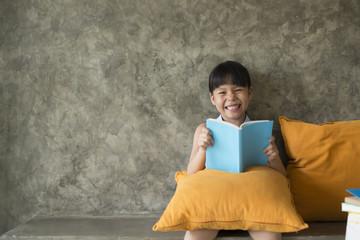 Smiling little girl reading book