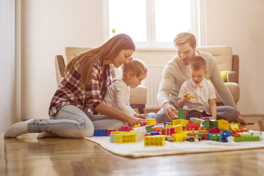 Parents with children having fun and playing together with toy blocks