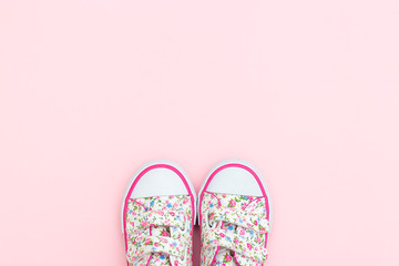 Sneakers for little girl in flowers and pink color on a pastel background. Copy space