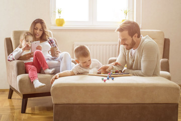 Parents with children having fun and playing together in living room