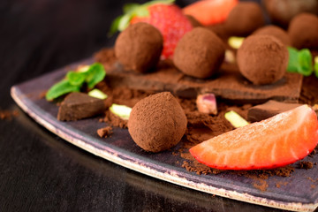 Chocolate truffles covered with cacao powder surrounded by strawberries and mint
