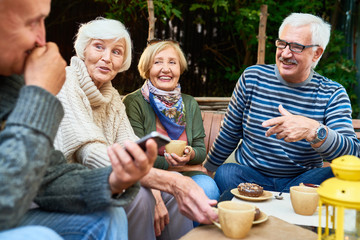Group of cheerful seniors enjoying time together drinking tea outdoors in cafe and sharing life stories in retirement Wall mural