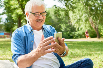 Portrait of cheerful senior man listening to music from smartphone enjoying sunny autumn day in park