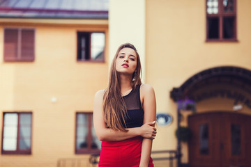Portrait of young girl with beautiful eyes outdoors. Woman in urban background.