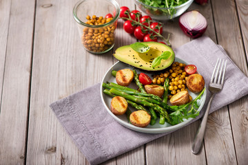 Healthy dinner with baked potatoes, green asparagus and spicy chickpeas, avocado, arugula, vegan, vegetarian food