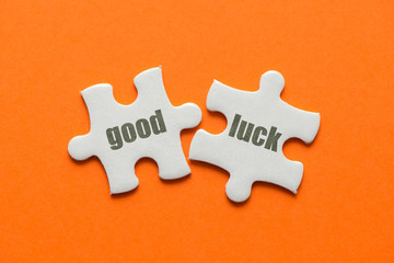 Wall Mural - The word Good Luck on two matching puzzle on orange background