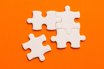 Wall Mural - Four white details of puzzle on orange background