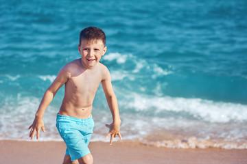 European boy is walking along the seacost.