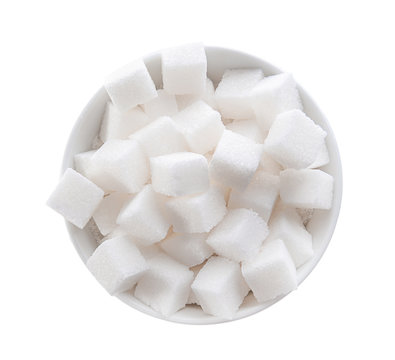 Refined sugar cubes in bowl on white background, top view