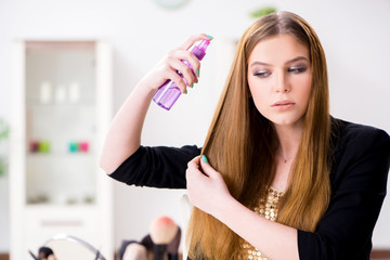 Young woman spraying hair polish to her hair