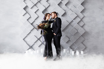 Wedding Couple, Bride and Groom fashion portrait, over gray volumetric background with copyspace. Dry ice smoke.