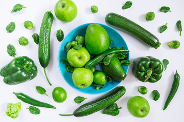 green vegetables and fruits on blue plate on white background. overhead view