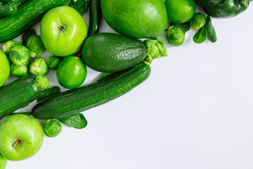 green fruits and vegetables on white background with copy space by diagonal