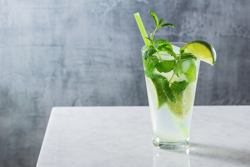 Mojito Cocktail with Mint and Limes in Glass on Marble Bar Counter with Copy Space