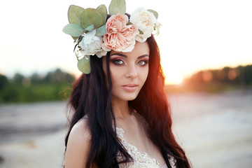 Woman with a wreath of flowers on her head and a summer dress walks through hills at sunset. Portrait of a brunette with long hair in rays of the setting sun, perfect makeup and beautiful blue eyes